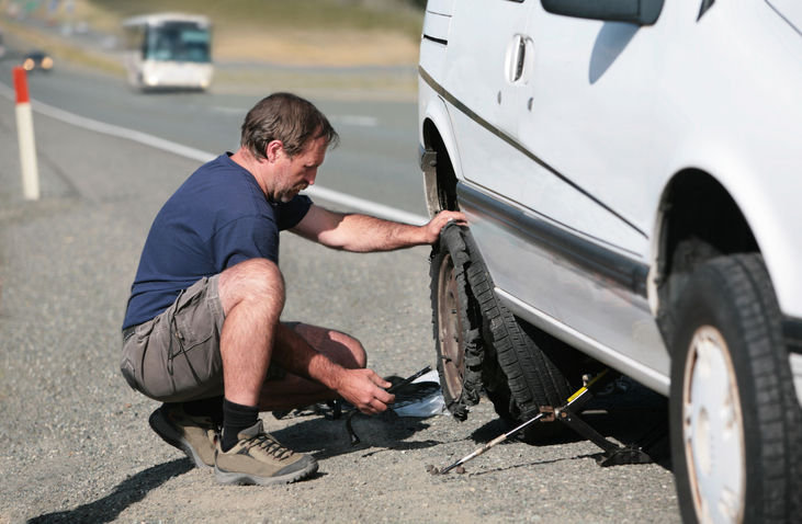 man on the side of the road fixing car